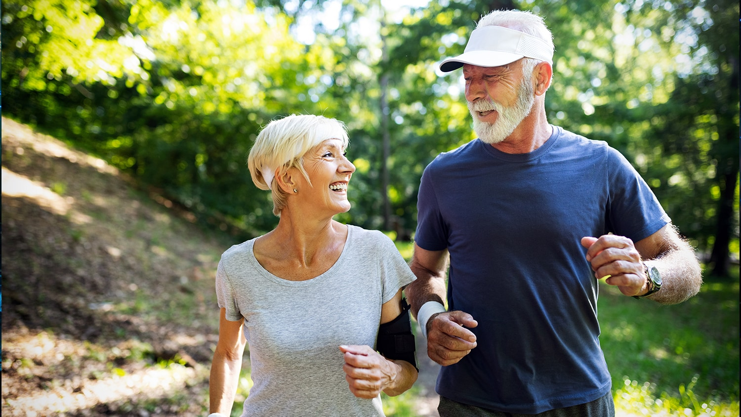 Older couple jogging in the woods